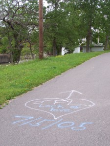 """Painted tag on the Canal Path near the west guard lock that says """"JPL Lock of Love"""" in a heart with an arrow pointing to the guard lock and the date 7/5/05."""